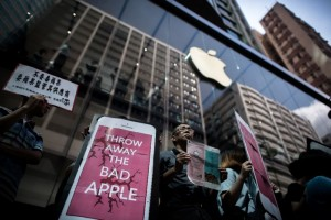 """Protesters gathered outside one of Apple's largest stores in Hong Kong on Friday morning, holding giant phones with the slogan ""Throw Away The Bad Apple"""