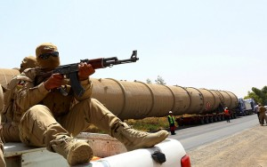 Caption:A section of an oil refinery is guarded as it is brought on a lorry to the Kawergosk Refinery, some 20 kilometres east of Arbil, the capital of the autonomous Kurdish region of northern Iraq, on July 14, 2014. The International Energy Agency (IEA) said on July 11, that an offensive by jihadists in northern Iraq had cut output by 260,000 barrels a day in June to 3.17 million, after fighting forced the closure of the country's biggest refinery and slashed production from the giant Kirkuk field. (Photo credit should read SAFIN HAMED/AFP/Getty Images)